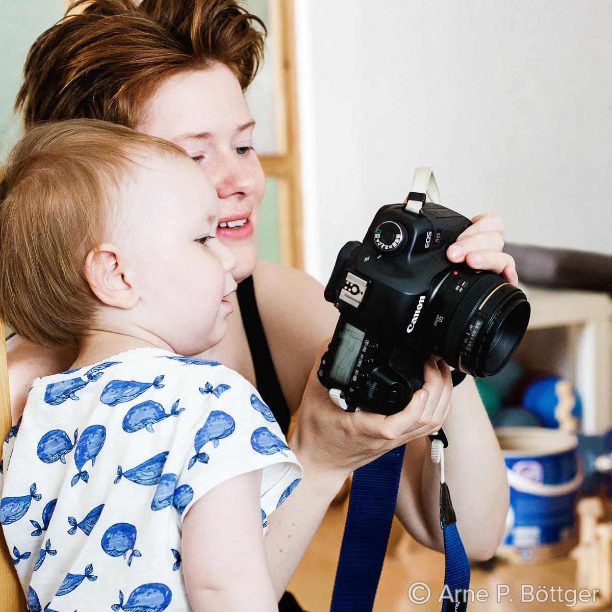 Fotografin zeigt einem Kind Bilder auf der Kamera