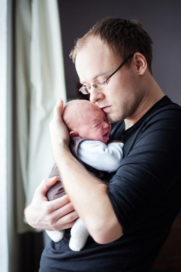 schreiendes Baby wird von seinem Papa sanft beruhigt