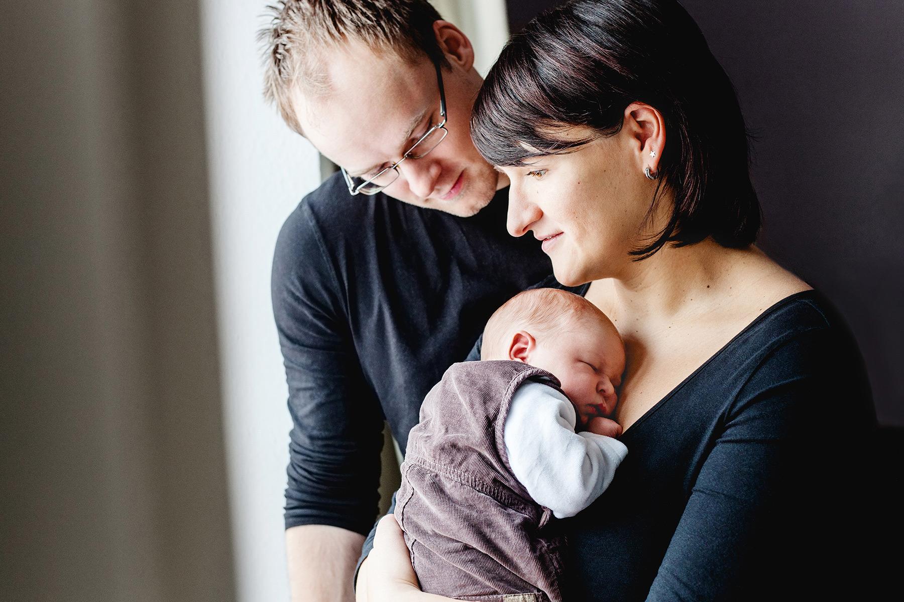 Eltern stehen gedankenversunken mit ihrem Baby am Fenster