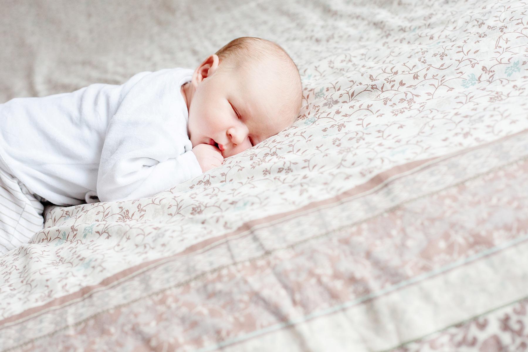 Baby liegt schlafend auf dem Bett seiner Eltern