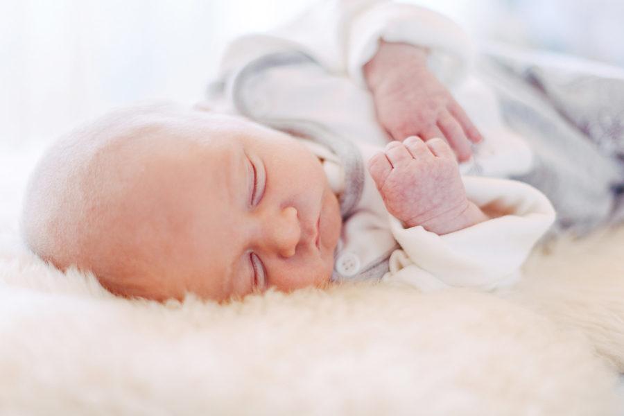 Baby liegt schlafend auf Lammfell