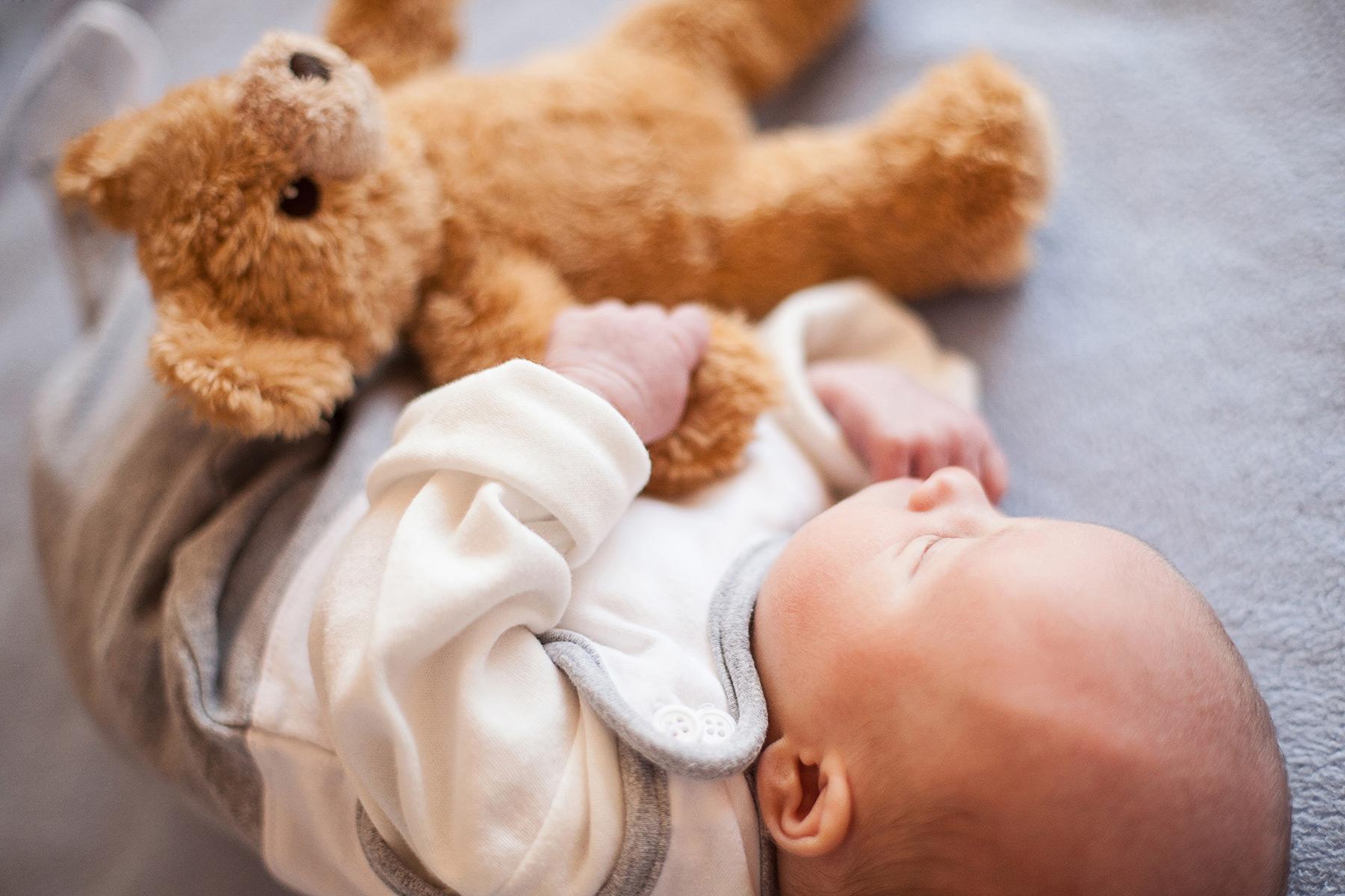 schlafendes Baby hält einen Teddy fest in seinem Händchen