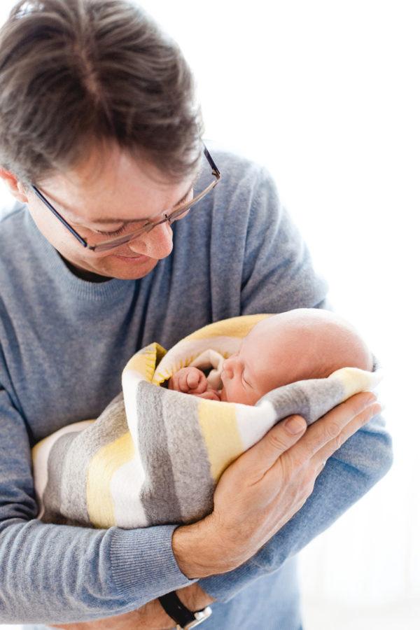 stolzer Papa hält sein Baby in eine Decke gewickelt auf seinen Armen und schaut es glücklich an