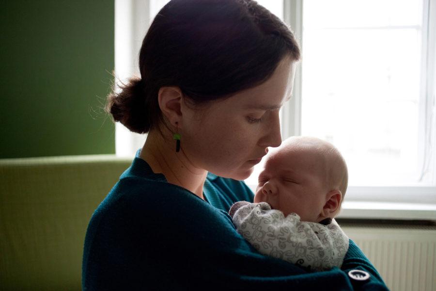 junge Mutter hält ihr Baby im Arm und sieht es beschützend an