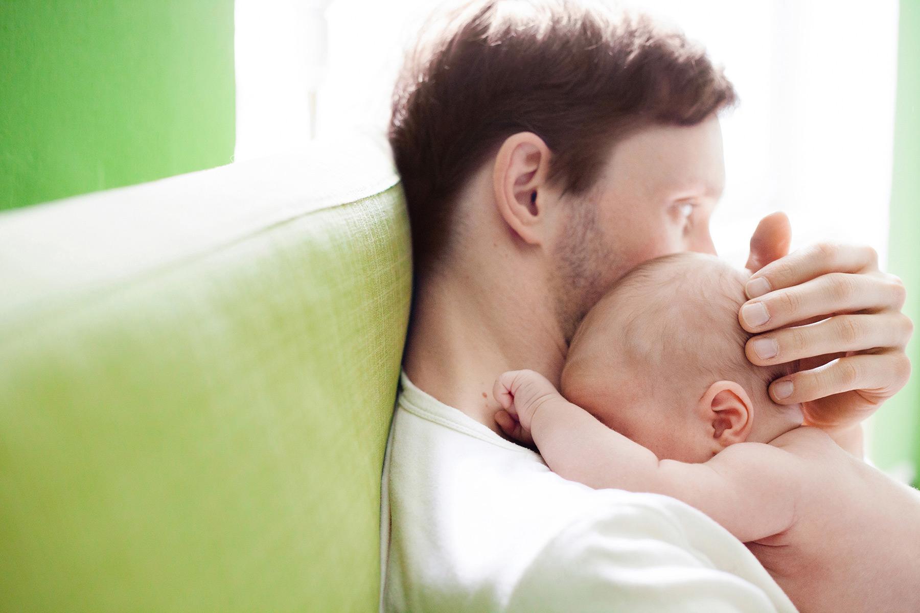 Papa hält sein Baby im Arm und streichelt sanft seinen Kopf