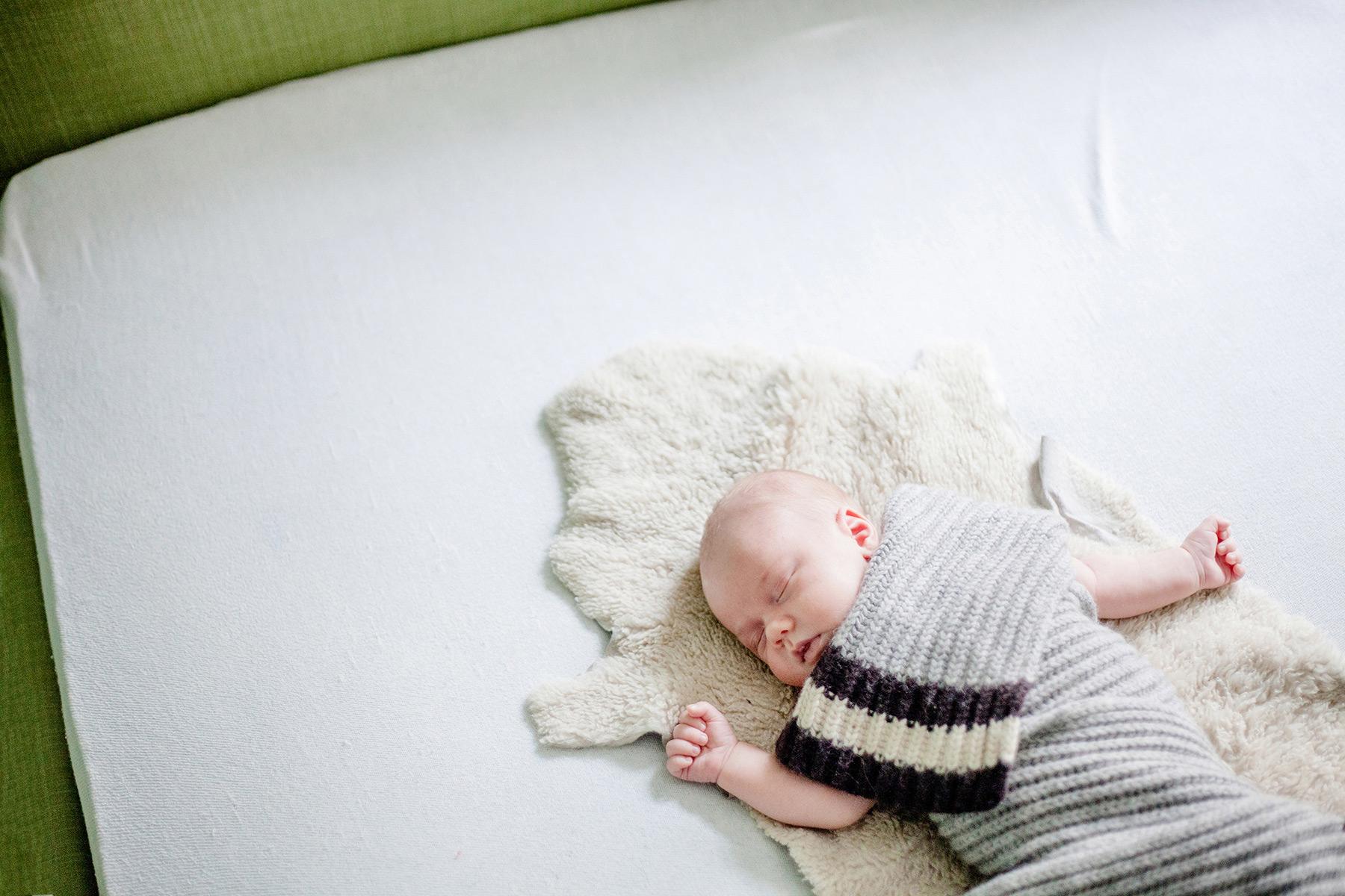 Baby liegt schlafend, von einem Schal bedeckt, auf einem Lammfell im Bett seiner Eltern