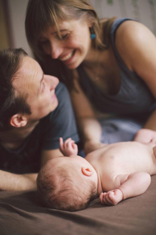 glückliche Eltern blicken sich verliebt an. Baby beobachtet sie dabei.