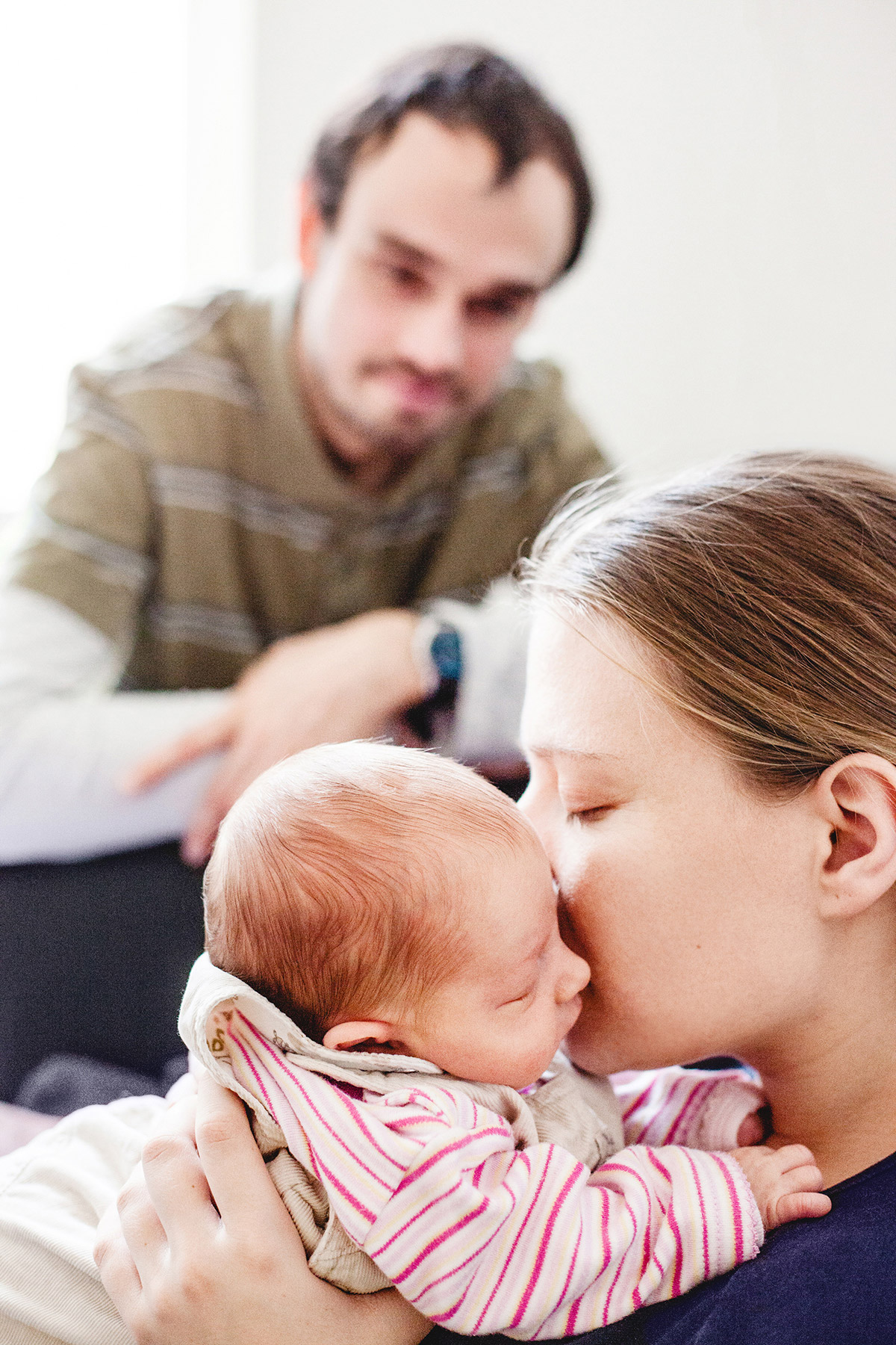 Mama küsst ihr Baby sanft auf die Wange. Papa beobachtet beide im Hintergrund.