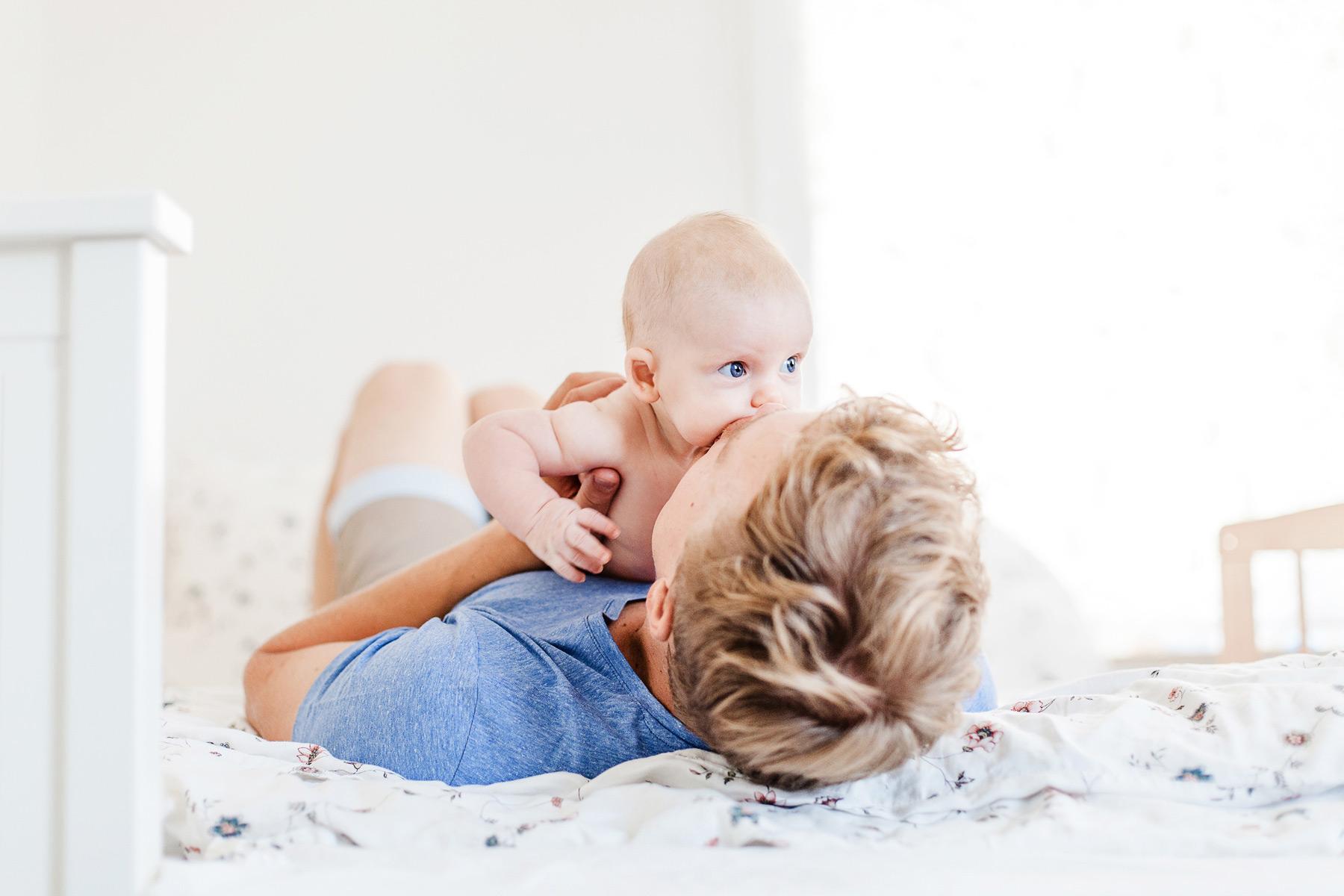 Papa liegt mit Baby auf dem Bett und küsst seine Wange
