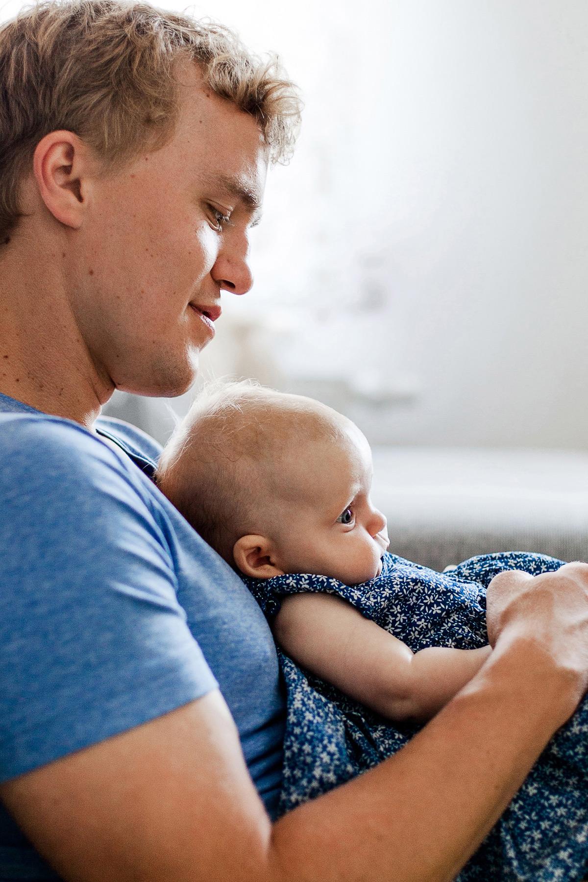 Baby lehnt an Papas Brust und Papa betrachtet es