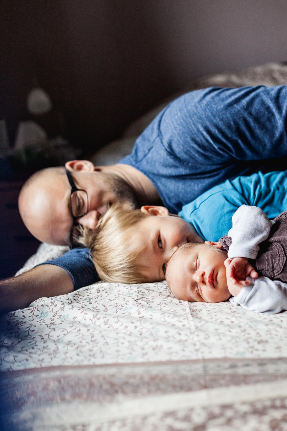 Papa liegt mit seinem großen und seinem kleinen Jungen auf dem Bett