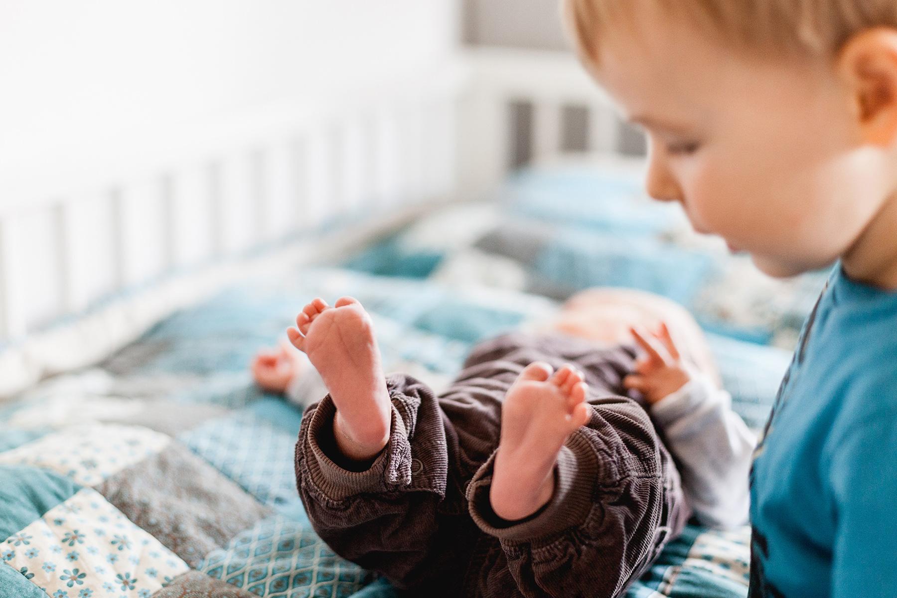 kleiner Junge schaut winzige Füßchen seines kleinen Bruders an