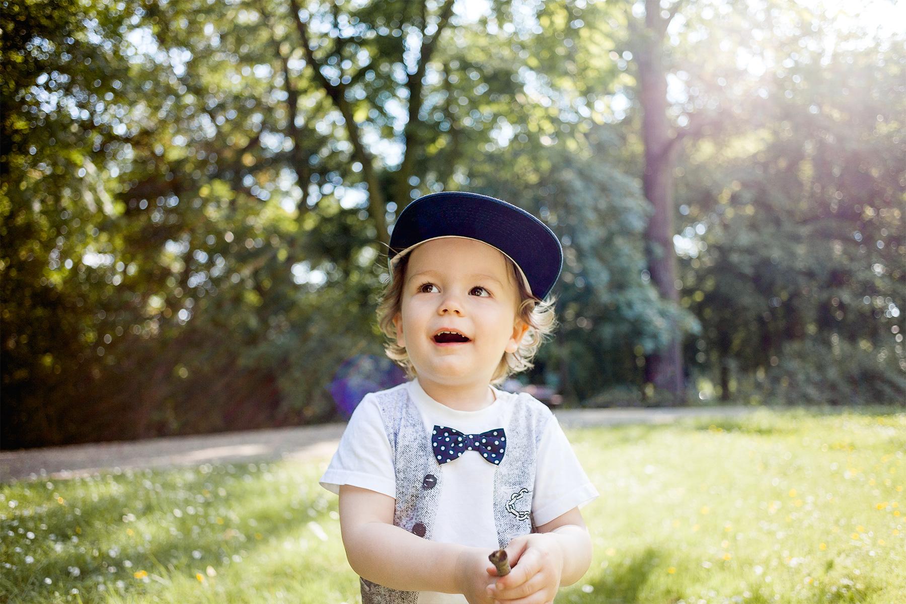 kleiner Junge steht mit einem Stock in den Händen im Park und blickt staunend ins Grün