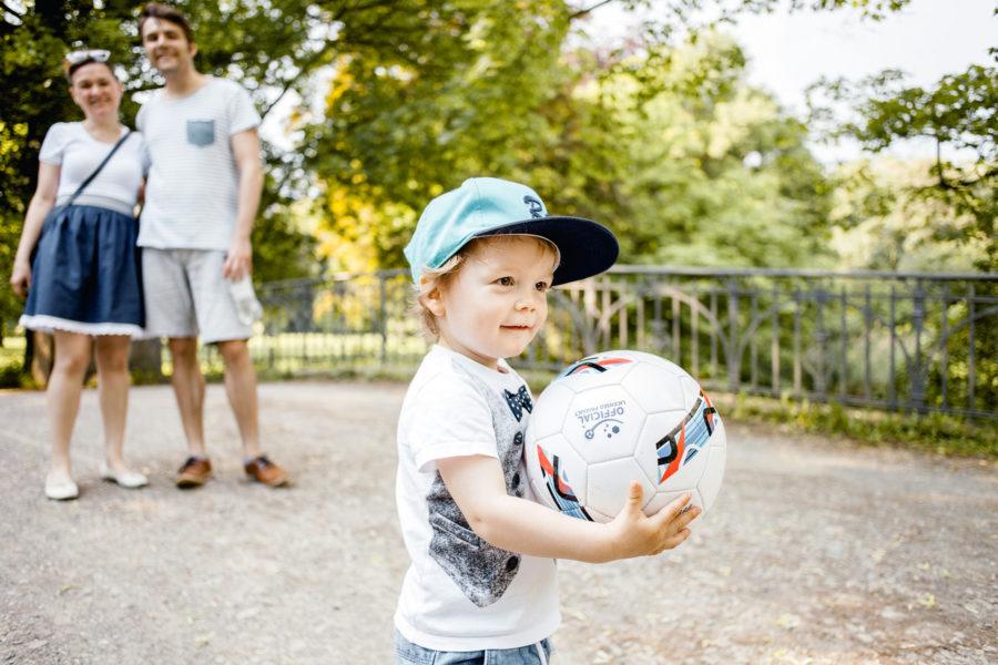 kleiner Junge steht mit seinem Fußball in den Händen stolz im Park. Eltern lächeln und beobachten ihn dabei.