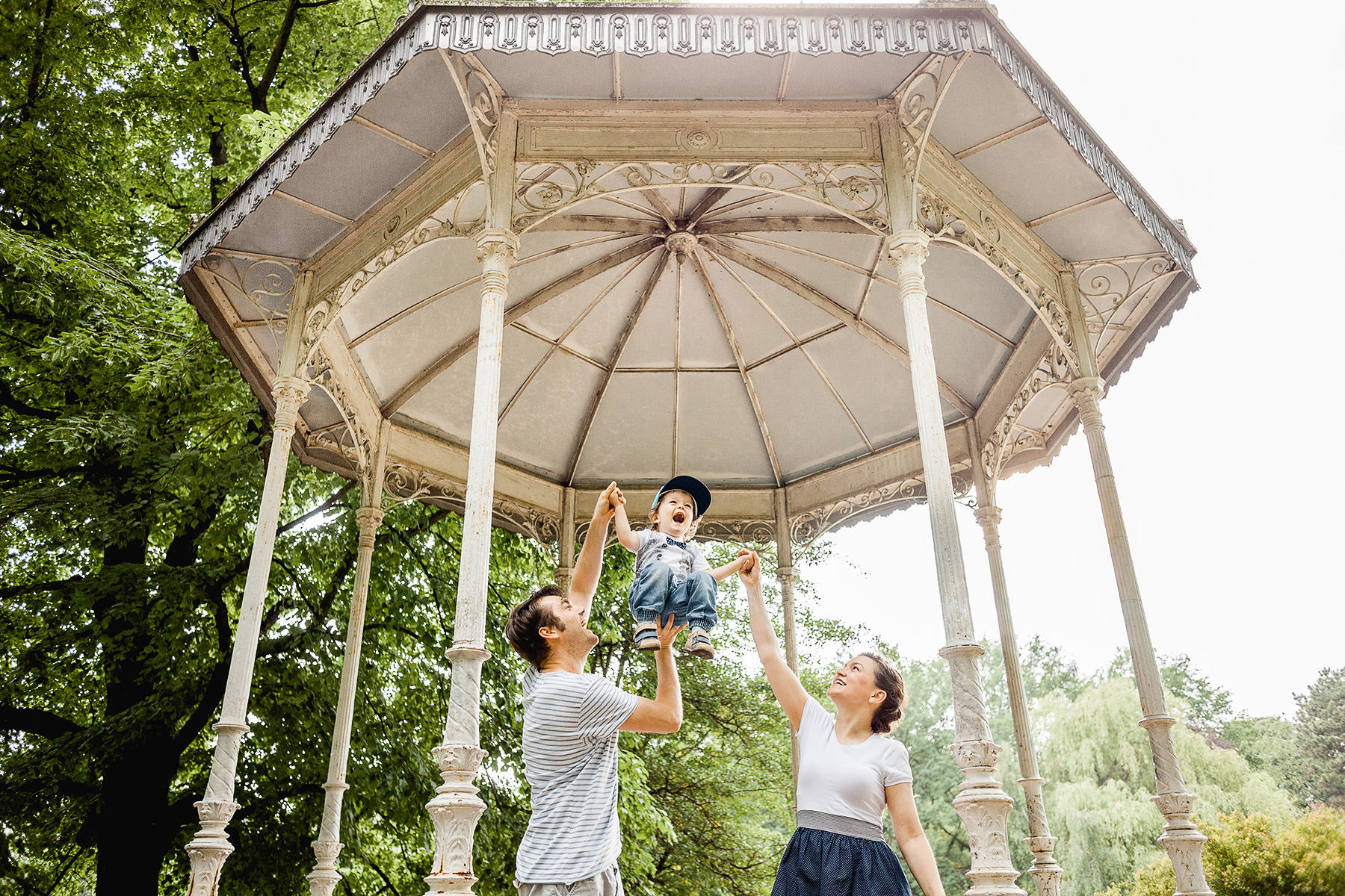 glückliche Familie spielt vor einem Pavillion im Palmengarten in Leipzig
