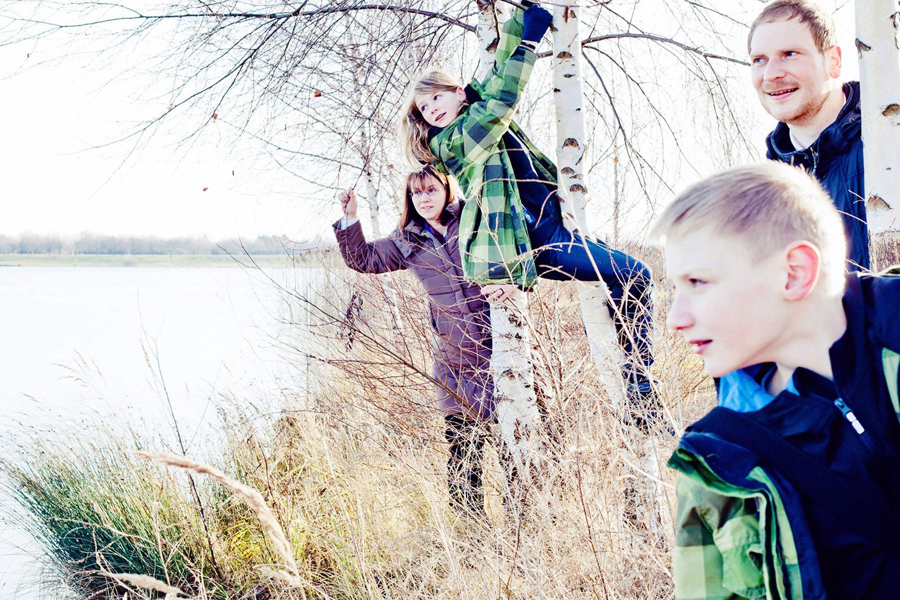 Familie steht zwischen Birken am Kulkwitzer See in Leipzig und genießt die Aussicht