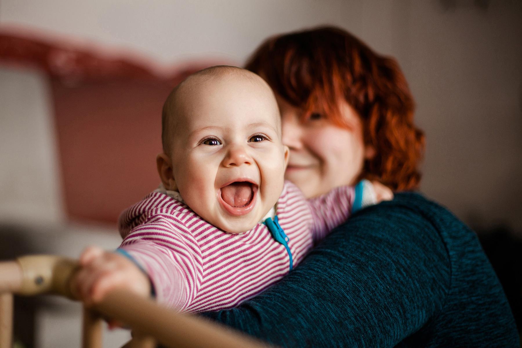 fröhlich lachendes Kleinkind wird von Mama gehalten