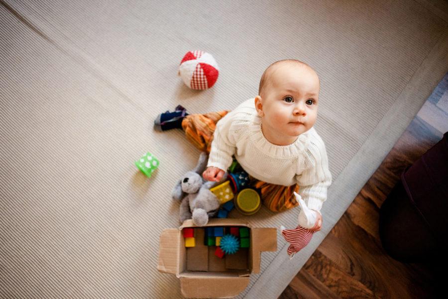 kleines Kind sitzt mit seinen Spielsachen auf dem Boden