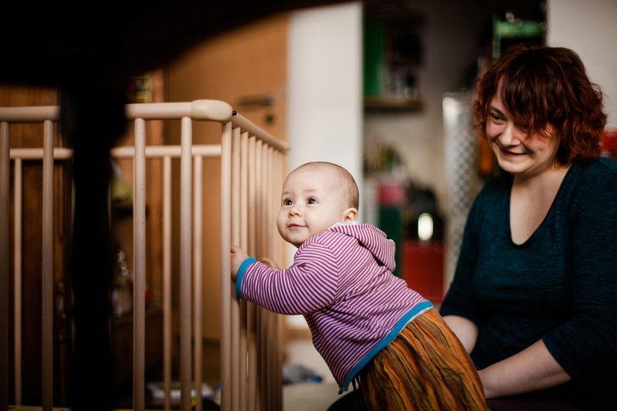 Kleinkind zieht sich an seinem Laufställchen hoch und erkundet das Wohnzimmer. Mama betrachtet es dabei lächelnd.