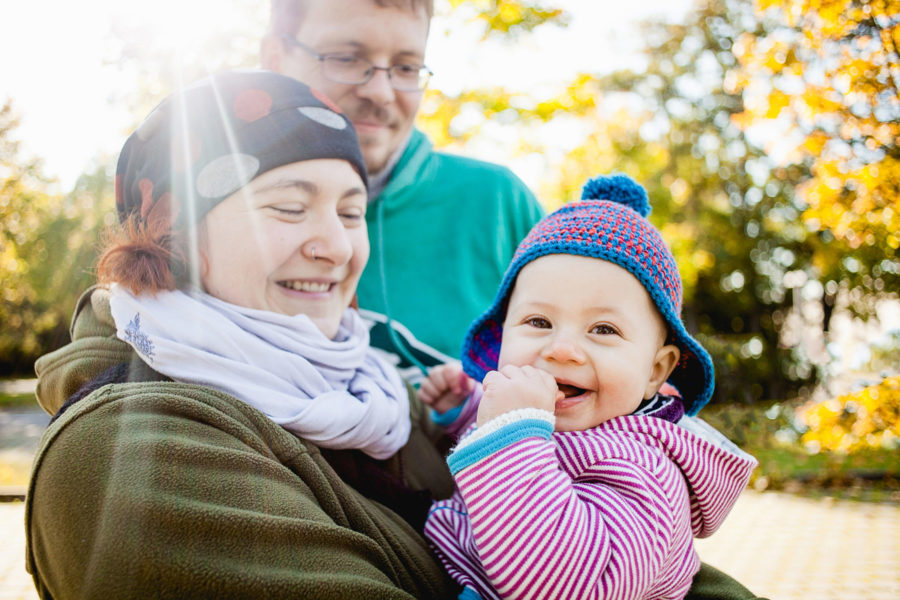 lächelnde Mama hält ihr Kleinkind auf dem Arm. Papa steht hinter ihnen und betrachtet sein Kind stolz