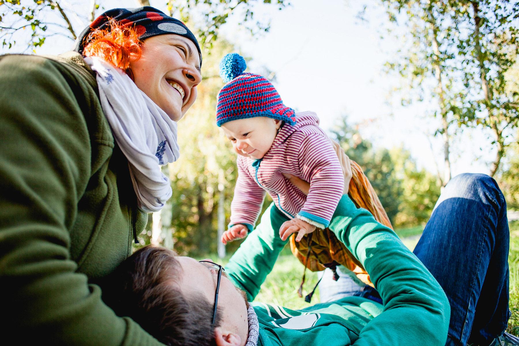 kleines Kind wird von seinem liegenden Papa hoch gehalten, während Mama lächelnd Papas Kopf in ihrem Schoß hält