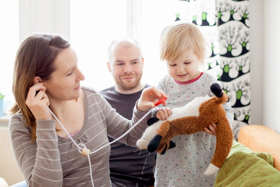 Mama und Papa spielen im Wohnzimmer gemeinsam mit ihrem kleinen Mädchen mit einem Kuscheltier