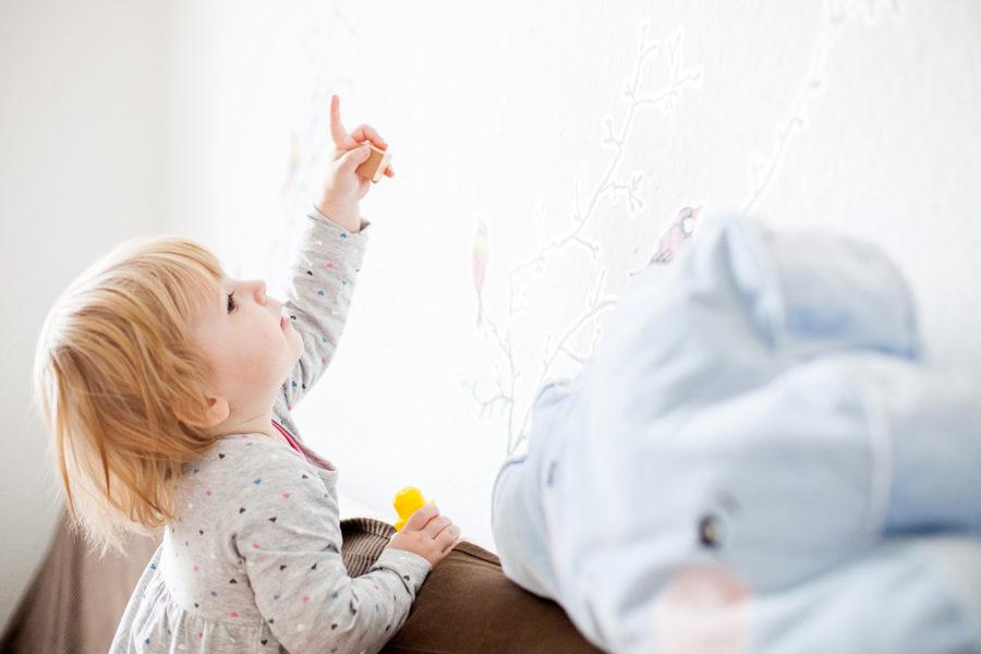 kleines Mädchen zeigt in seinem Kinderzimmer auf ein Wandbild
