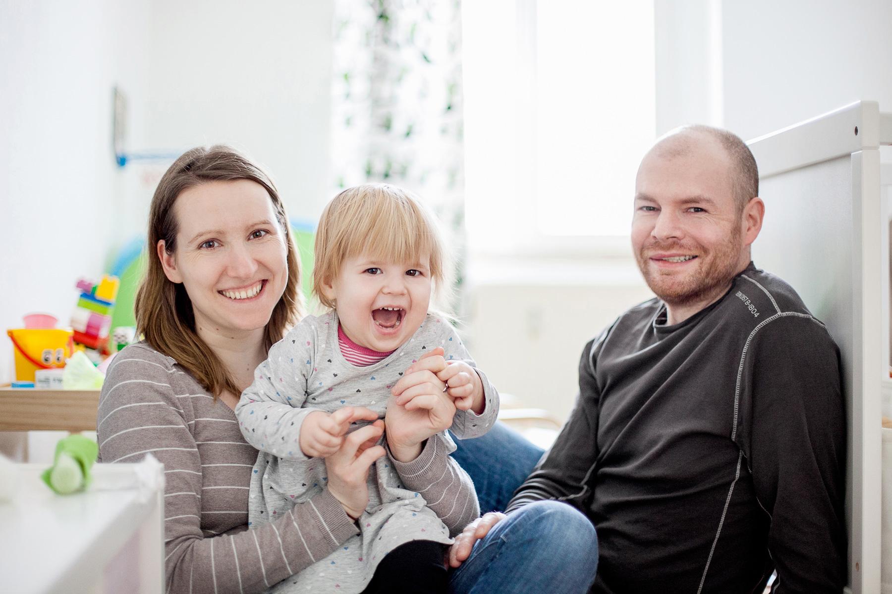 glückliche Familie mit Kleinkind sitzt lachend im Kinderzimmer