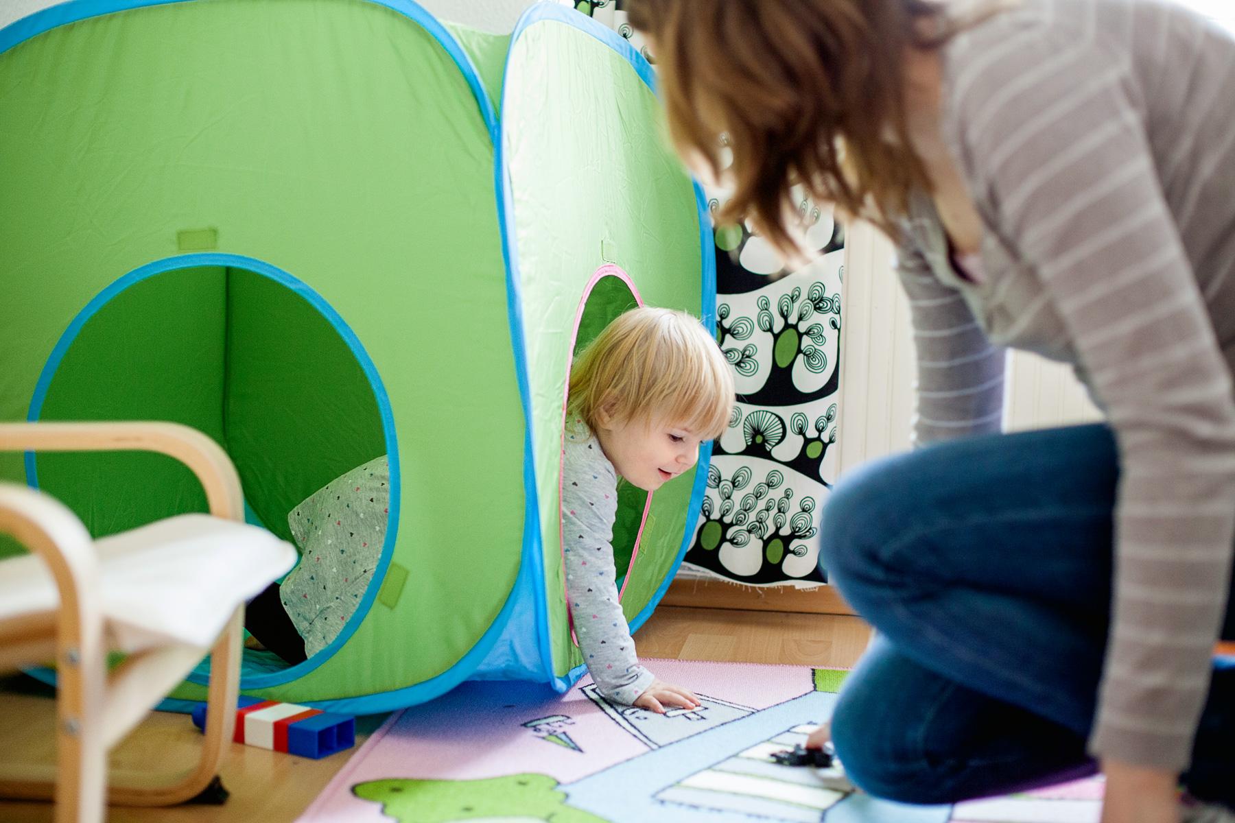 Mama spielt mit ihrer kleinen Tochter Verstecken im Kinderzimmer
