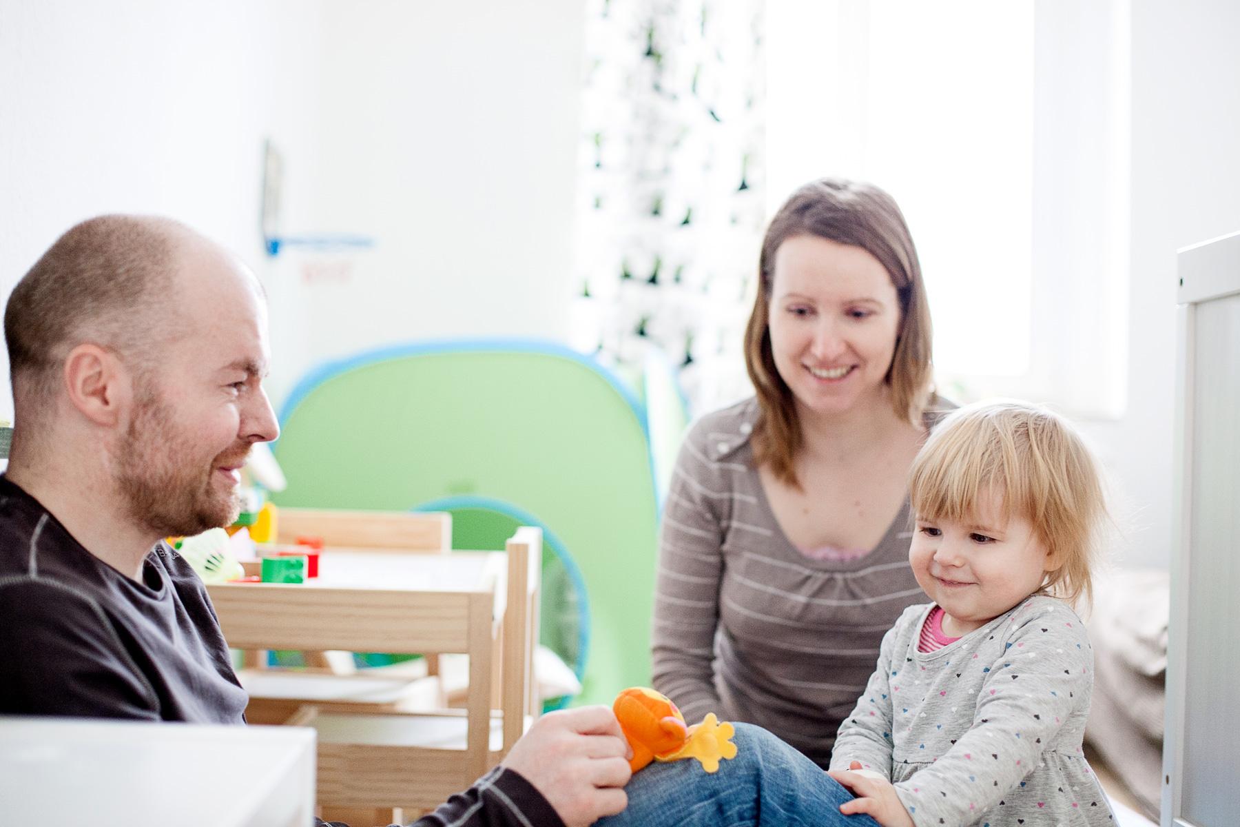 Papa und Mama spielen mit ihrem kleinen Mädchen im Kinderzimmer