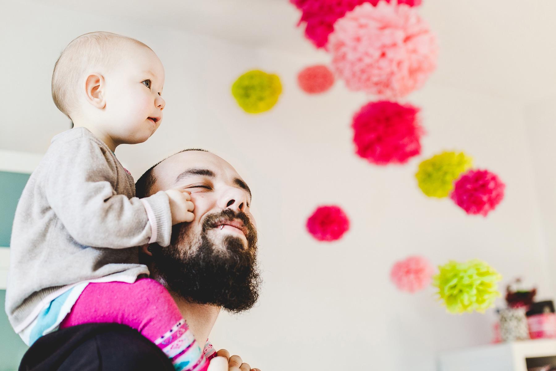 kleines Kind sitzt auf Papas Schultern und streichelt sein Gesicht