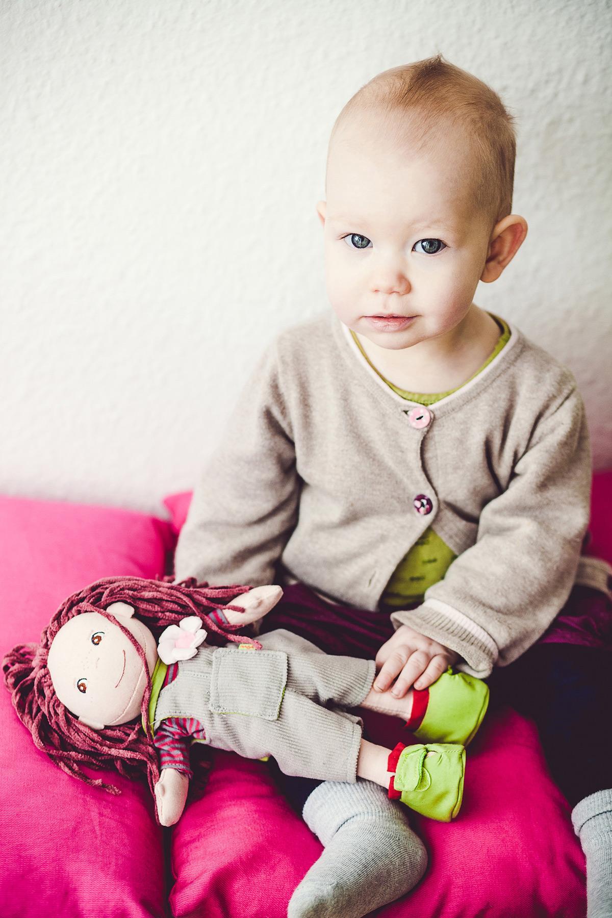 kleines Kind sitzt mit seiner Puppe auf pinkfarbenen Kissen