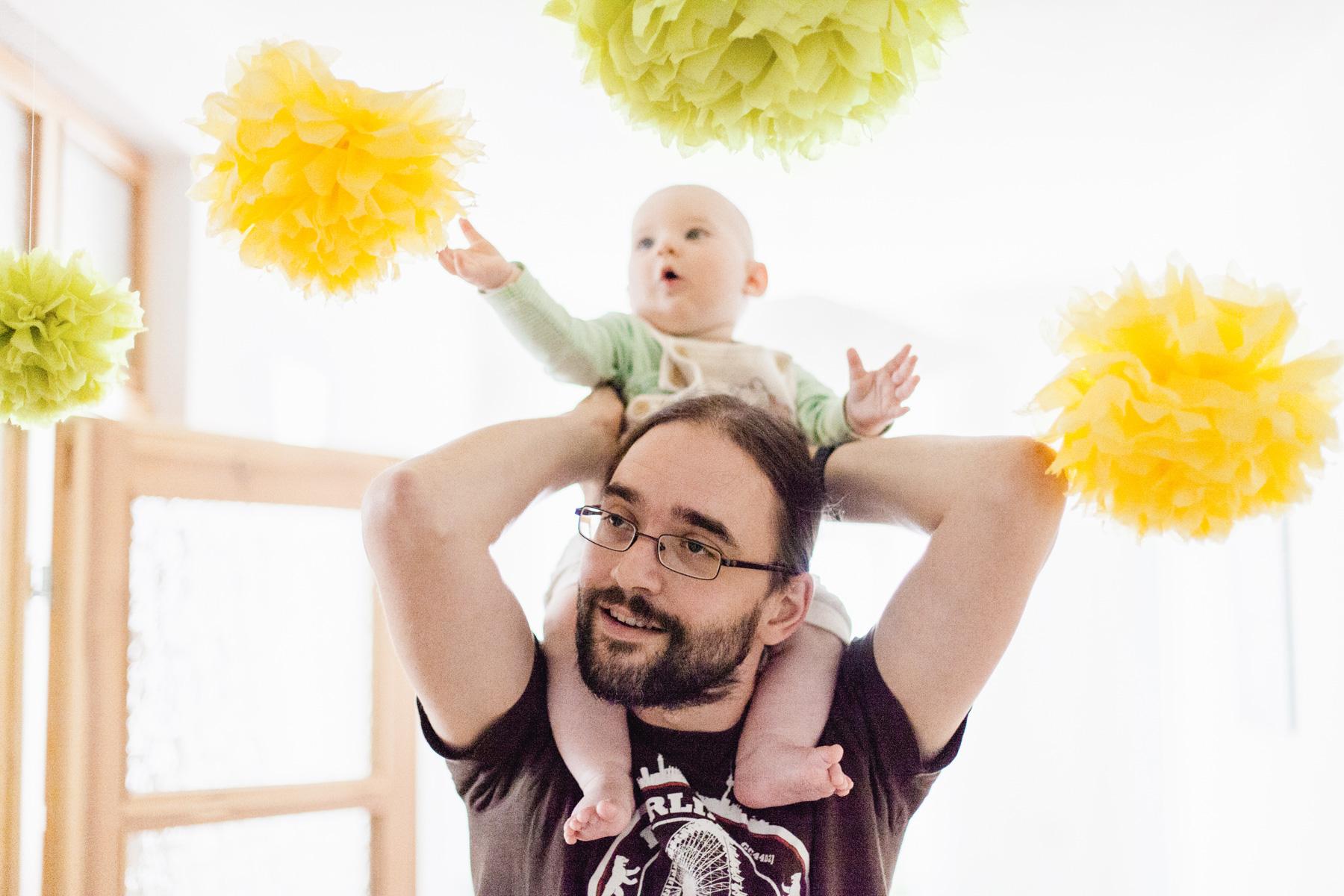Baby sitzt auf Schultern von Papa und bestaunt Pom Poms