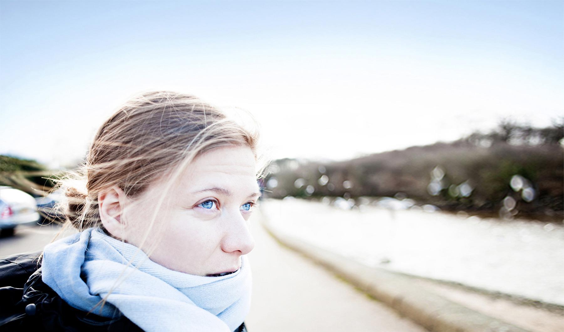 junge Frau steht nachdenklich an einem kühlen Wintertag am Fluss