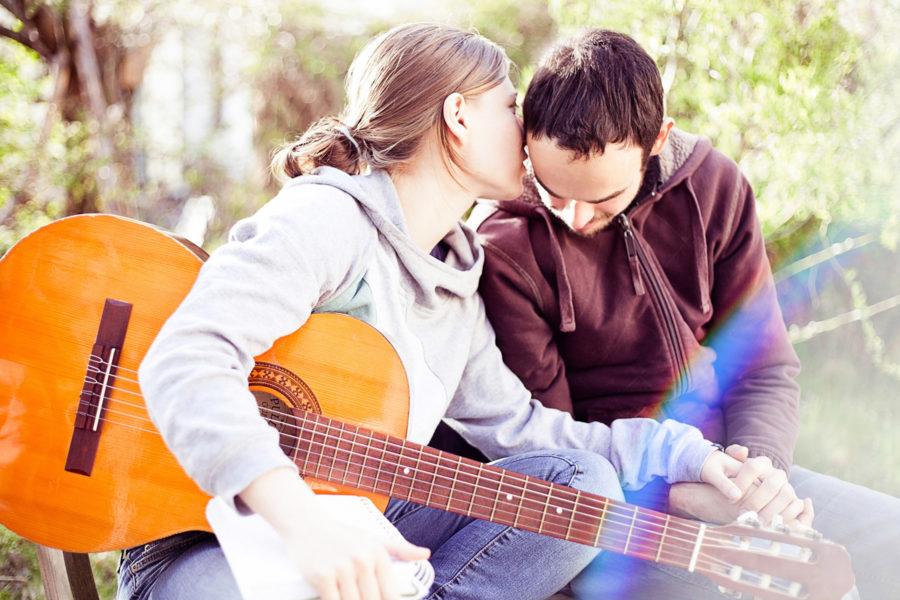 junge Frau mit Gitarre, hält die Hand ihres Freundes und flüstert ihm ins Ohr