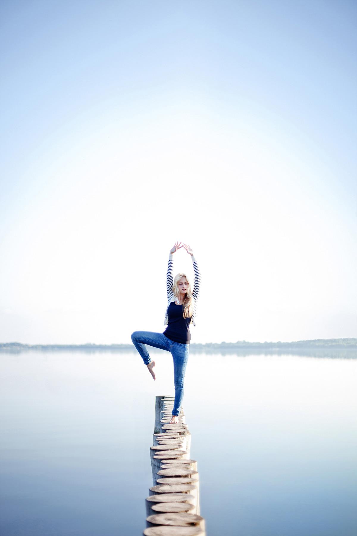 junge Frau steht in Yoga-Pose am See