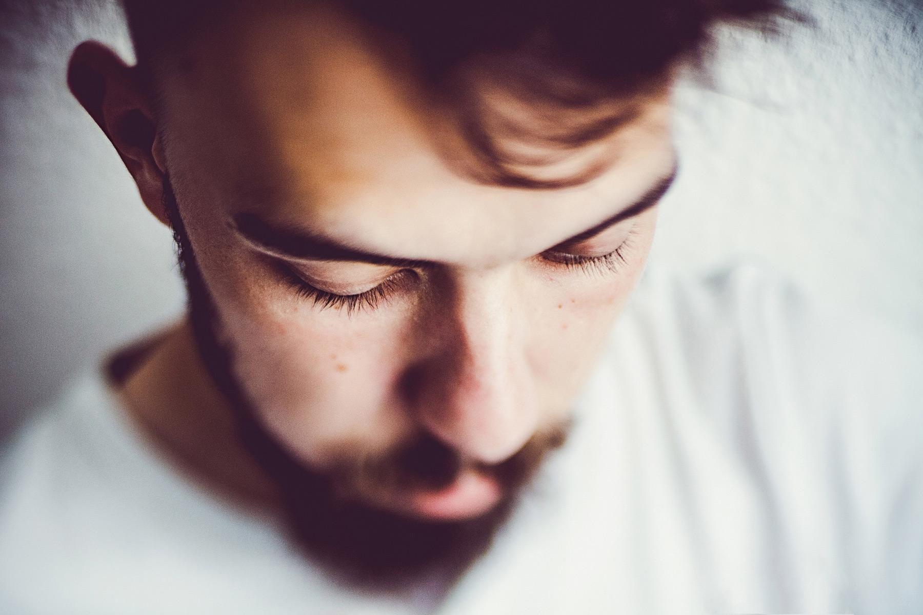 junger Mann blickt gedankenverloren zu Boden