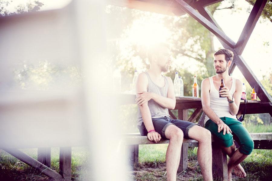 zwei Freunde trinken ein Bier im Freien und unterhalten sich dabei