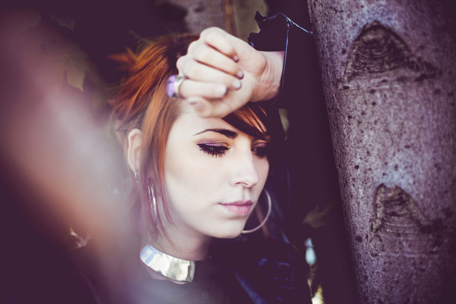 junge Frau lehnt gedankenversunken an einem Baum