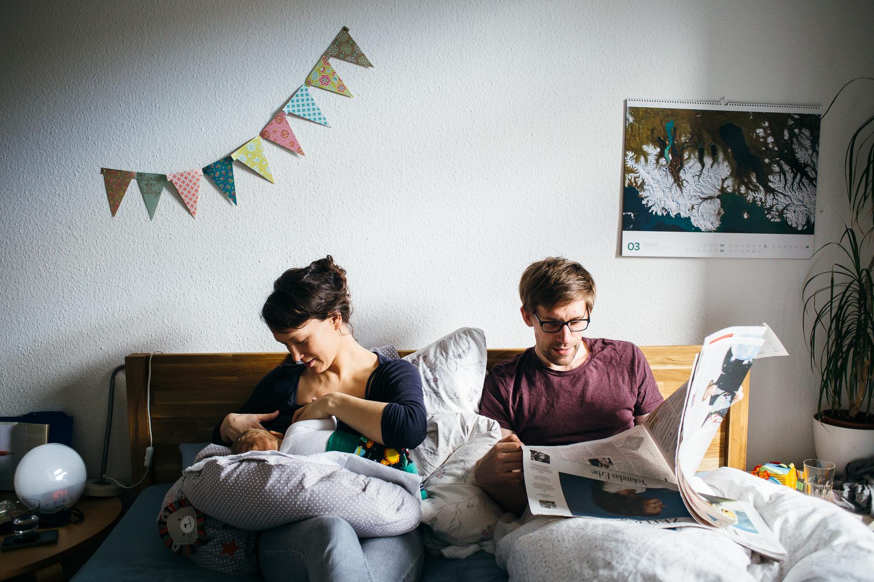 Papa liest Zeitung im Familienbett, daneben sitzt Mama und stillt das Baby