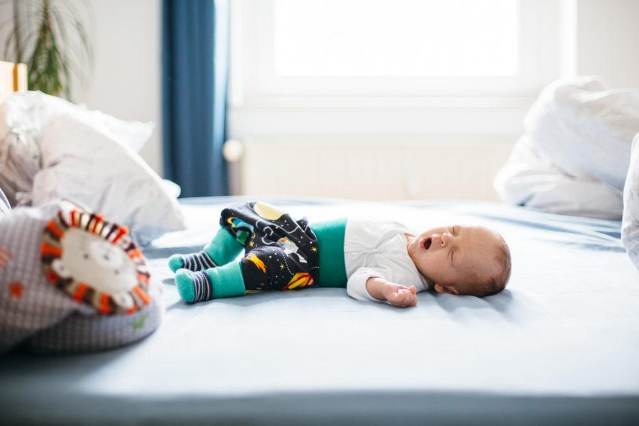 Baby liegt gähnend im Familienbett