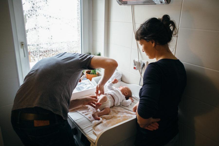 Papa wickelt sein Baby unter Mamas kritischem Blick