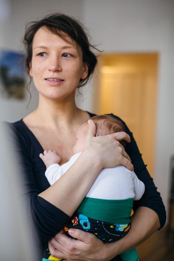 Mama hält ihr Baby gedankenversunken im Arm