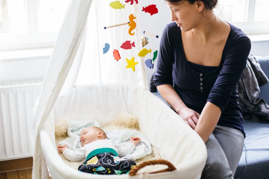 Mama betrachtet ihr friedlich schlafendes Baby