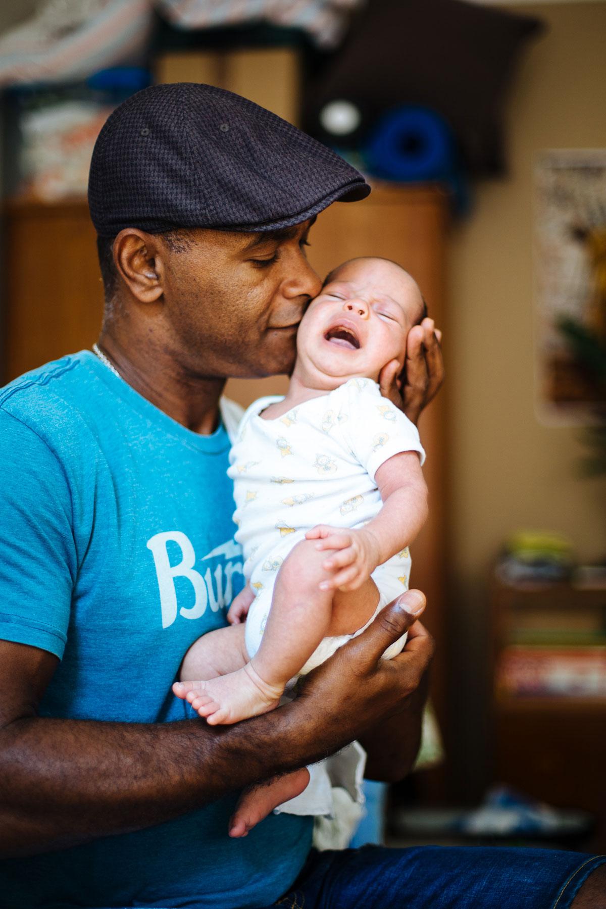 entspannter Papa tröstet weinendes Baby