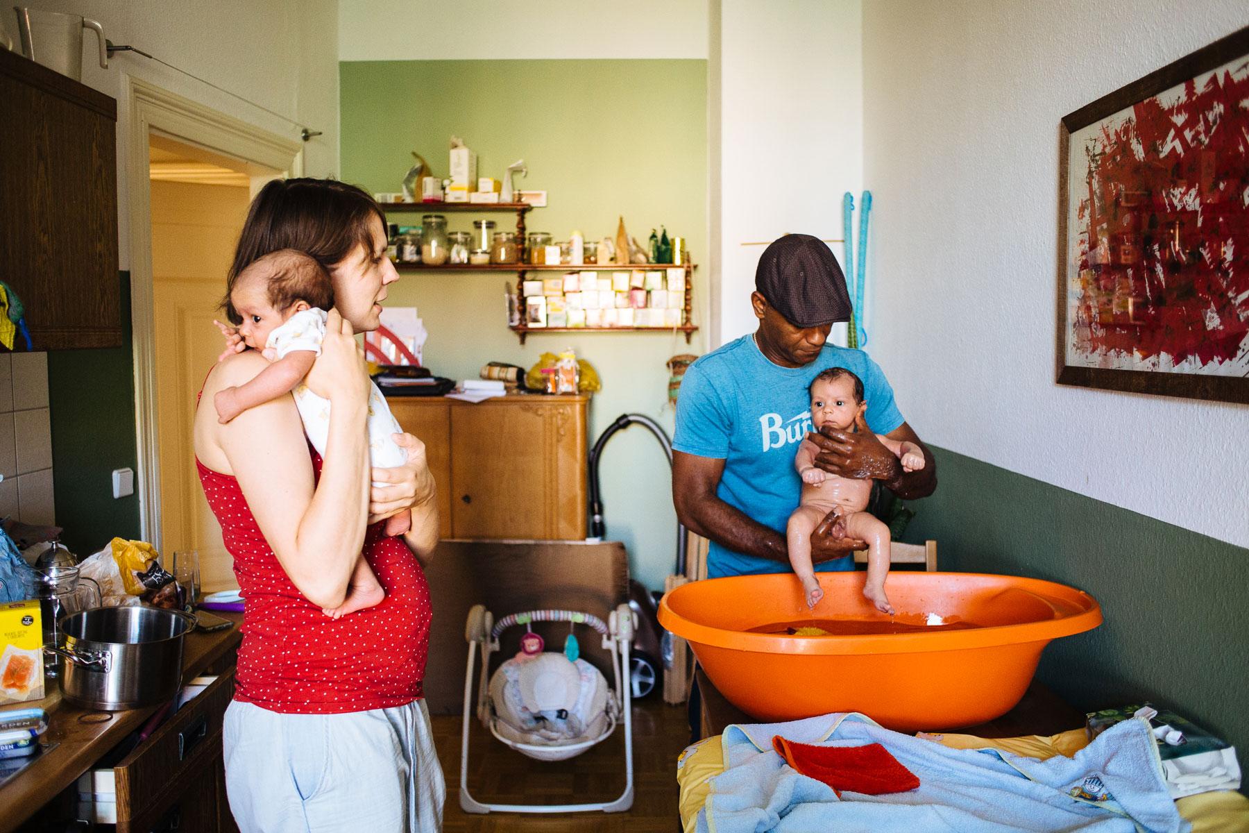 Familie mit Zwillingen beim Babybaden in der Küche