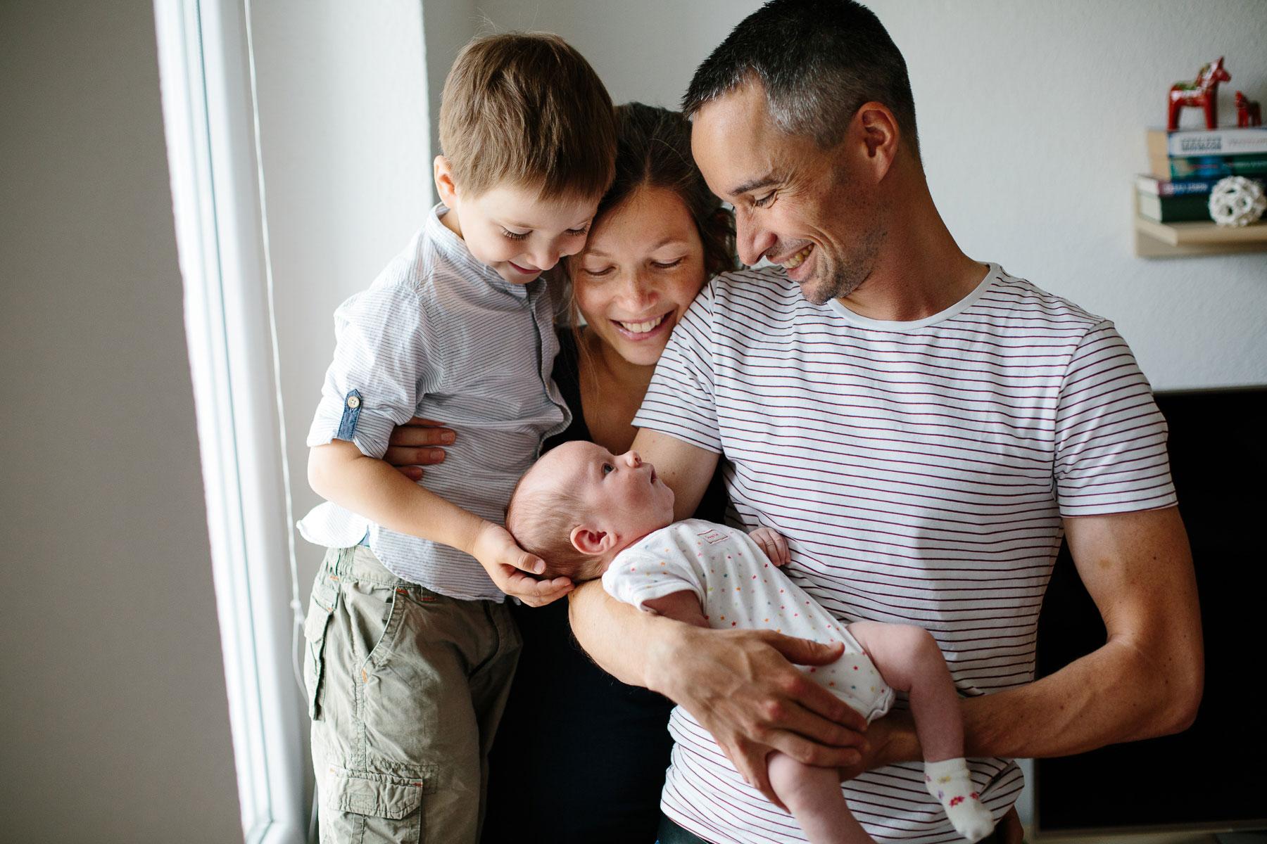 Baby wird von Mama, Papa und großem Bruder angelächelt