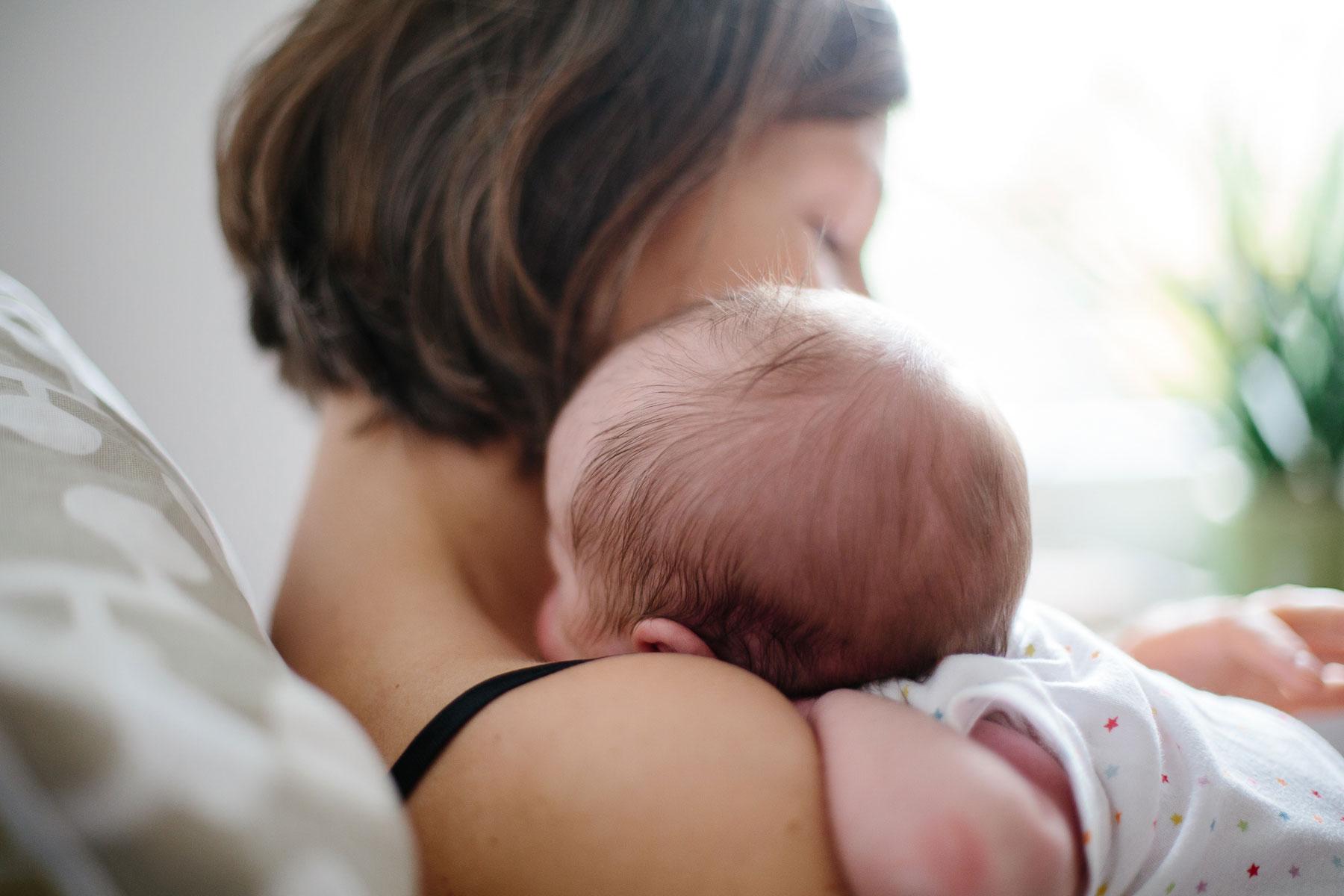 Nahaufnahme von Baby liegend an Mamas Schulter