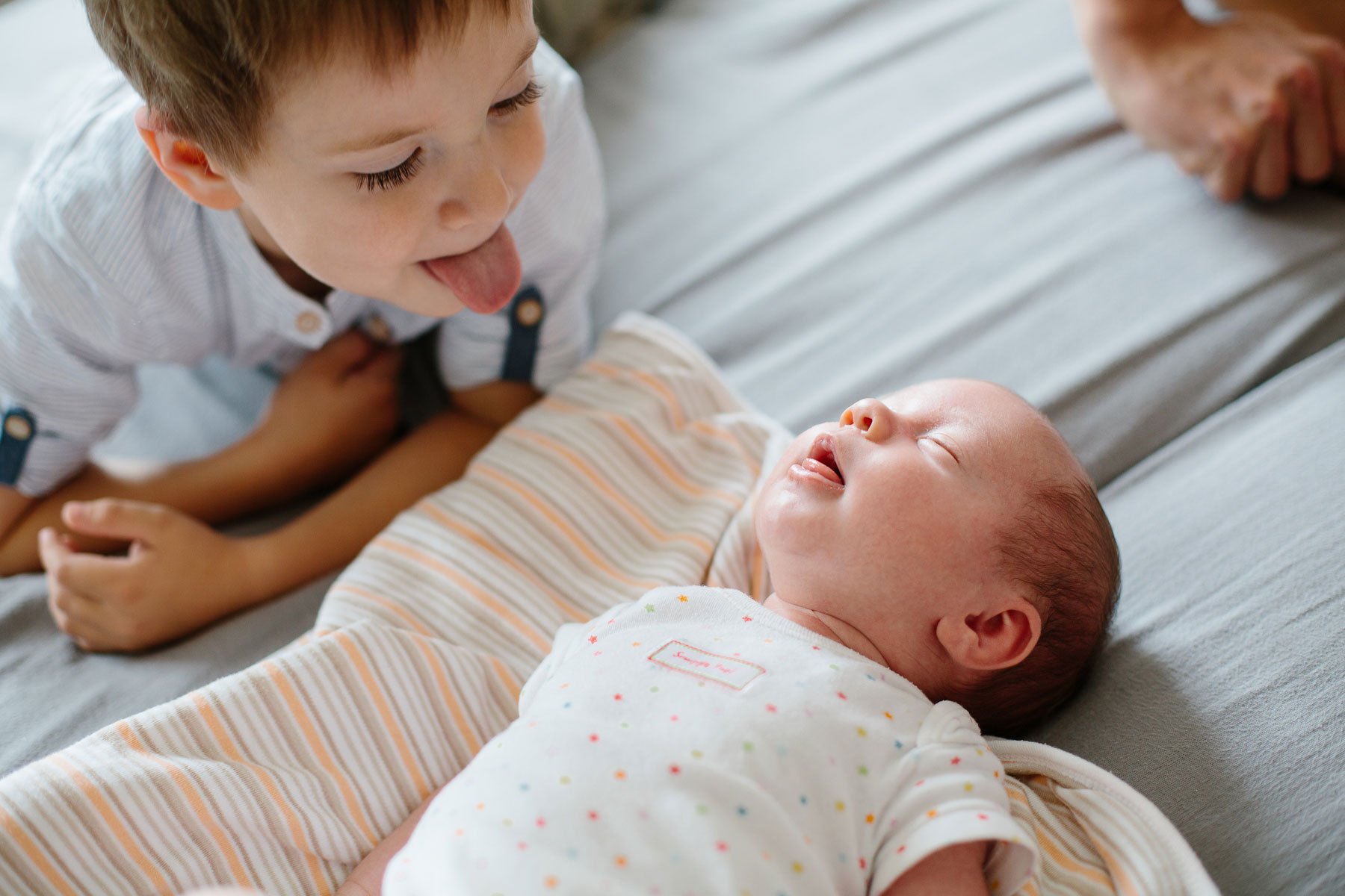 älterer Bruder und Baby strecken beide ihre Zungen heraus